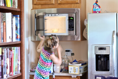 My daughter uses the microwave on a stool while baking.