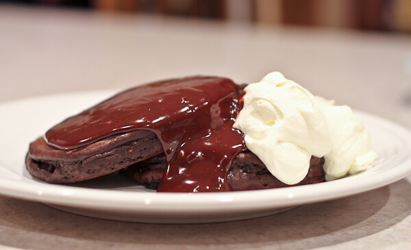 Chocolate Ganache Poured over Chocolate Pancakes with whipped cream